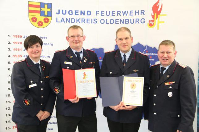 Thomas Heuermann (2.links) und Sascha Meister (2. Rechts) erhielten bei dem Kreisjugendfeuerwehrtag jeweils eine Ehrung von Werner Mietzon (rechts). Diane Febert gratulierte. / Bild: Bahrs
