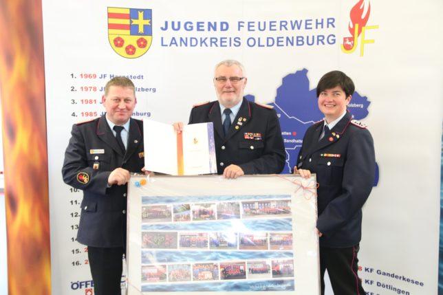Werner Mietzon (links) verlieh Peter Sparkuhl die Ehrennadel der Deutschen Jugendfeuerwehr in Gold. Diane Febert (links) überreichte eine Bildercollage. / Bild:Bahrs